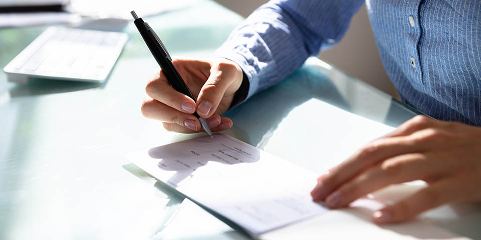 woman signing a paper check
