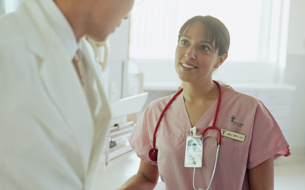 A female nurse or doctor smiling and talking to a male doctor wearing a white coat