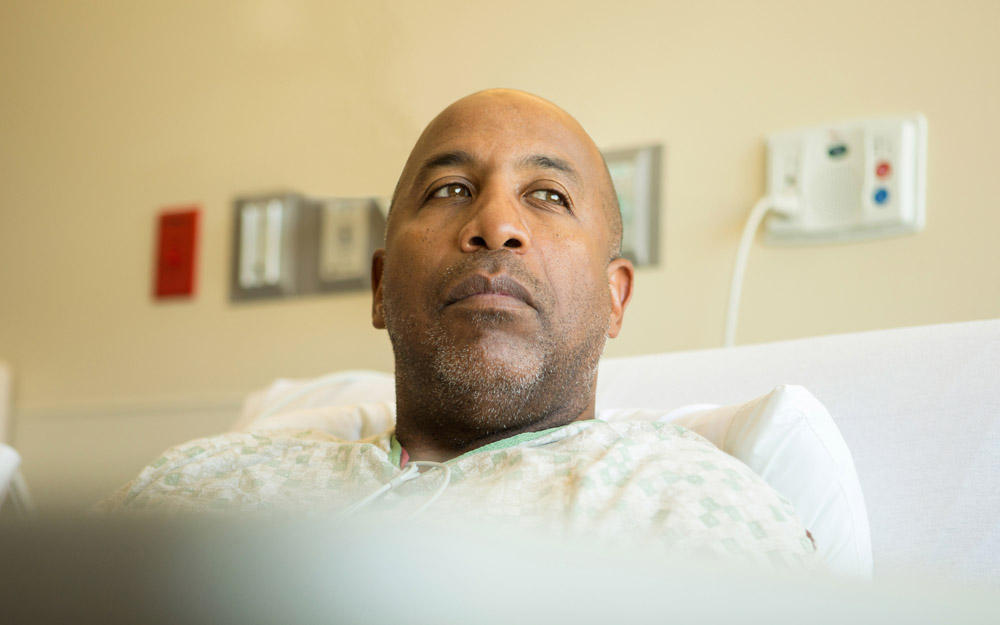 African-American male patient lying in a hospital bed, looking contemplative