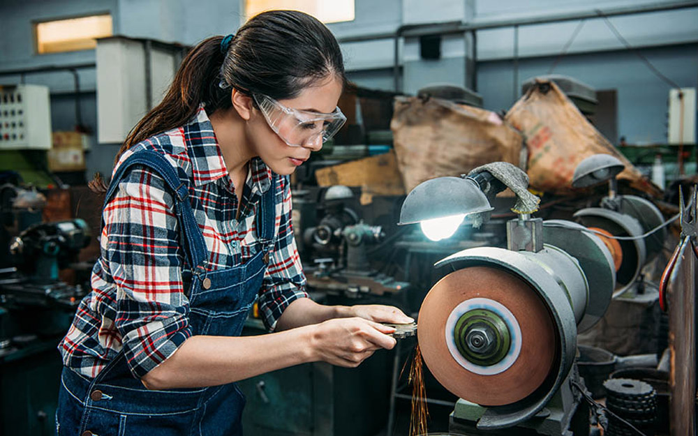 An Asian woman in a factory wearing safety goggles grinding a piece of metal