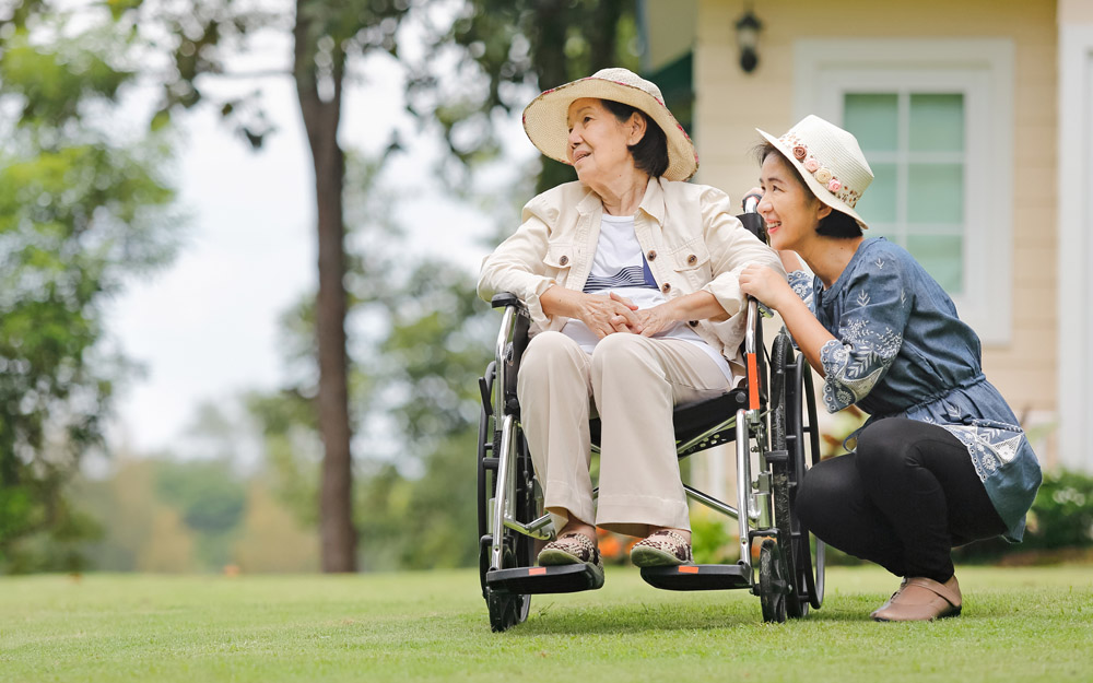 Smiling elderly Asian woman in a wheelchair in front of her house, with her daughter kneeling beside her