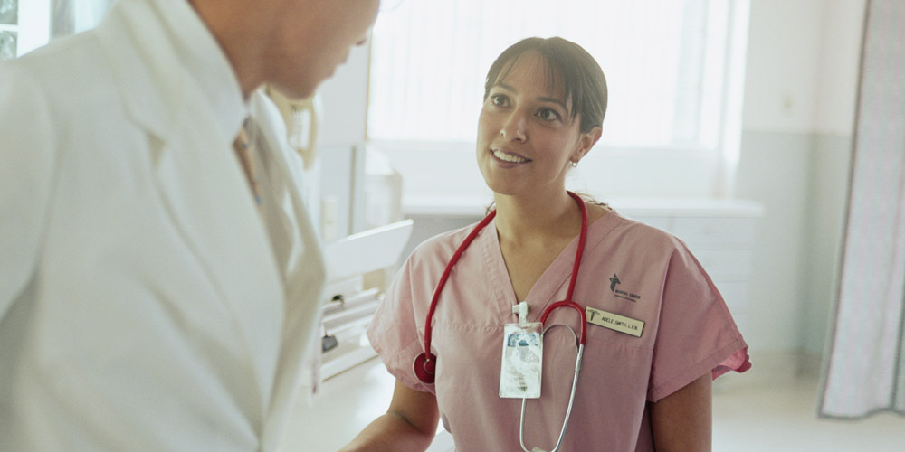 A female nurse or doctor talking to a doctor in a hospital setting.