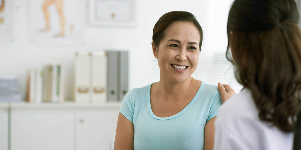 Asian woman in her doctor's office, smiling and talking to the doctor, who has a hand on the woman's shoulder