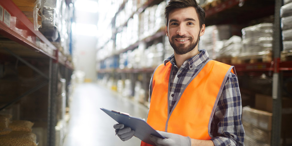 A warehouse supervisor standing with a clipboard in hand, smiling
