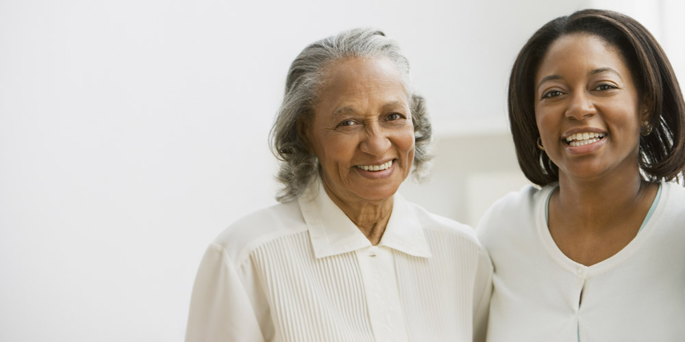 An elderly African-American woman and her mother, standing together, smiling