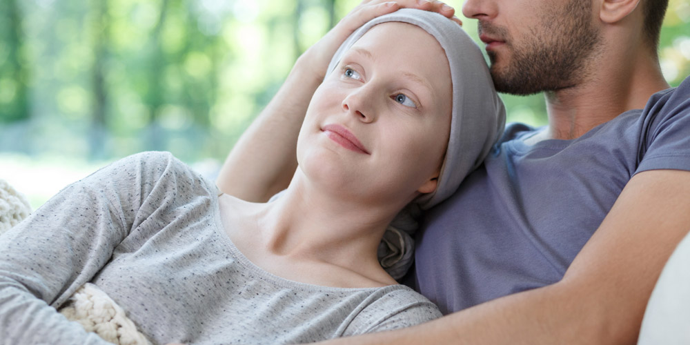 A woman who has lost her hair while undergoing chemotherapy smiling while leaning back against a man who is embracing her and holding the top of her head