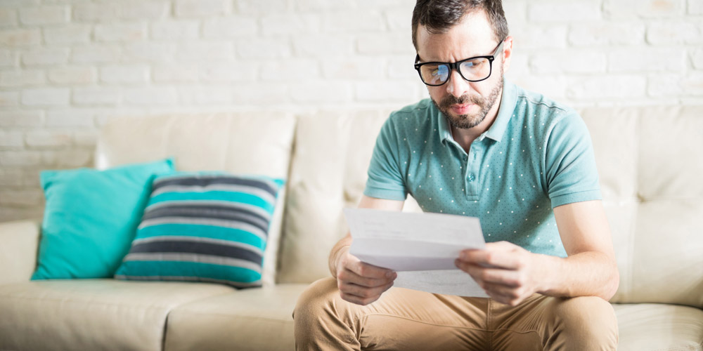 A man sitting on a sofa opening mail, looking confused