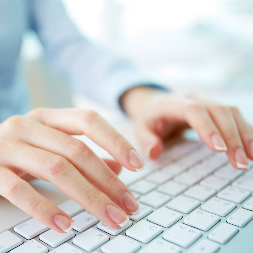 businesswoman's hands typing on a keyboard