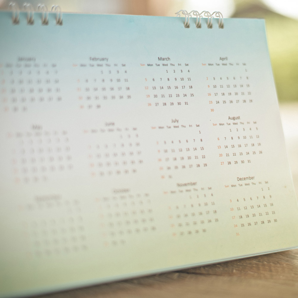 A printed desk calendar showing all 12 months at a glance