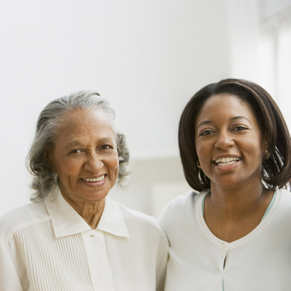 An elderly African-American woman and her daughter standing together and smiling