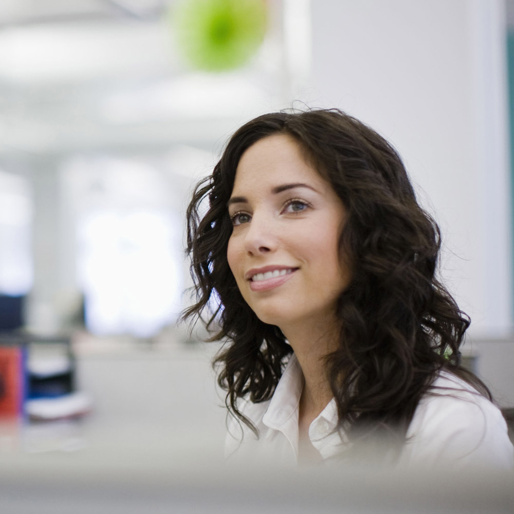 picture of a female office worker sitting at her desk, smiling