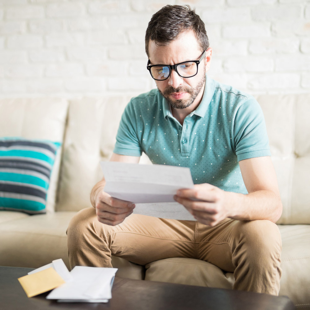 A man on a sofa opening mail and looking confused