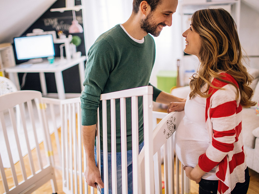 pregnant woman and her partner assembling a crib together