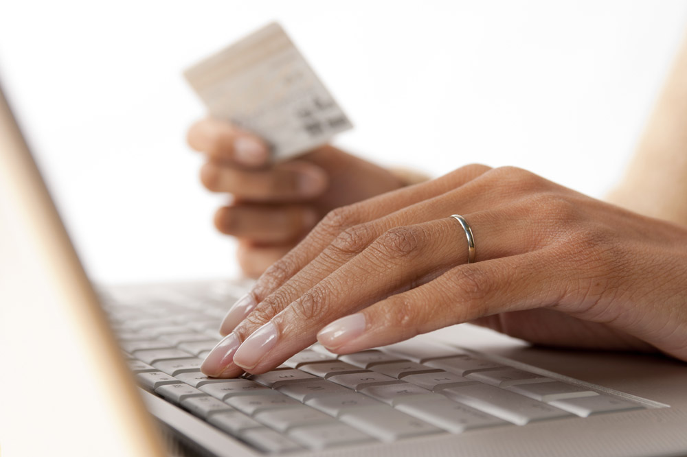 woman holding a debit card while sitting at a computer