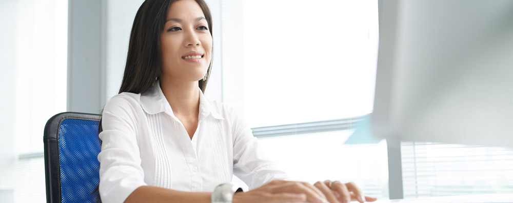 Smiling Asian woman sitting at a desk in front of a computer in a modern office