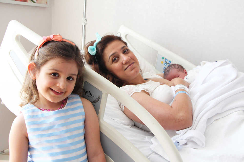 Mother in hospital bed holding newborn, with an older child standing next to the bed, smiling